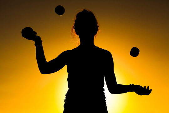 Silhouette of a Woman Juggling with Balls at Sunset