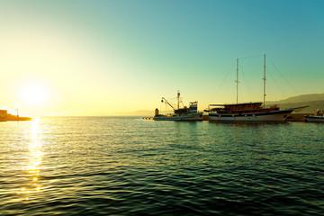 Fishing trawler and a sailboat moored in the harbor of a small town Postira - Croatia, island Brac