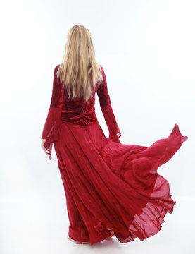 beautiful lady with long blonde hair wearing a red medieval fantasy gown. standing, isolated on white background.
