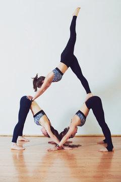 Three young women practicing acro yoga in white studio.