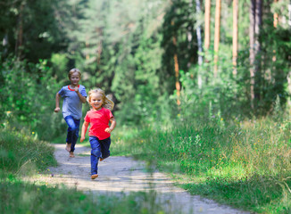 happy little girl and boy run play in summer nature