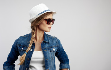 Beauty portrait of young pretty girl wearing sunglasses, hat and denim clothes posing in studio over grey background.