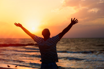 Silhouette of a man raising his hands to the sky at sunset on the beach
