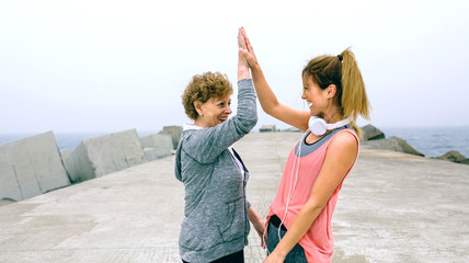 Senior sportswoman and female friend high five by sea pier