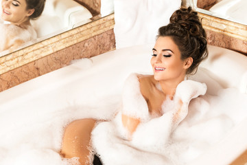 Happy and beautiful woman is taking bath with a foam
