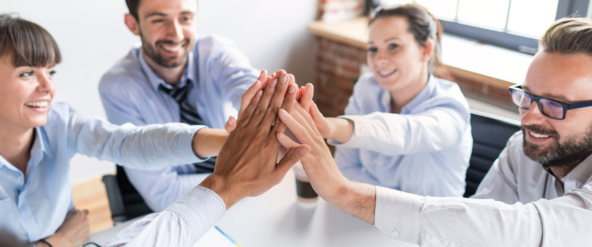 Happy business team giving high five in office.