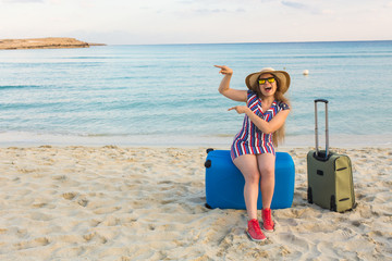 Happy laughing woman tourist with suitcases near the sea and pointing on copy space. Travel and summer vacation concepts