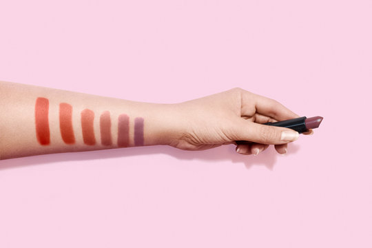 Female hand holding lipstick and color swatches painted on hand