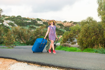 Happy traveler woman with suitcase on the beach. Concept of travel, journey, trip