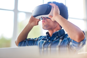 Young man with goggles having curious experience in virtual reality