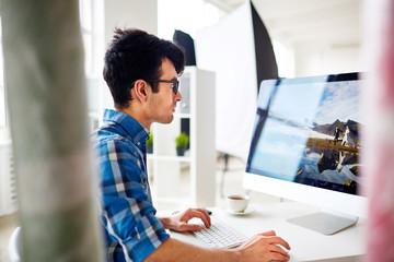 Creative designer or stock photographer retouching digital images in production studio