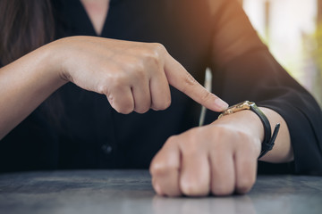 A business woman pointing at a black wristwatch on her arm in working time while waiting for someone with feeling angry