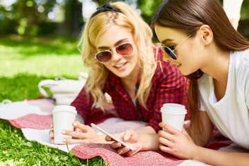Y-generation girls searching in smartphone and having drinks while relaxing in park