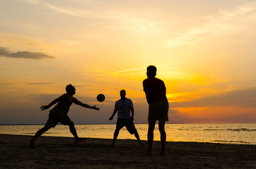 Silhouette of men playing beach volleyball at sunset.