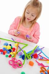 fillette 6 ans jouant avec des pompons de couleurs et des fils chenille