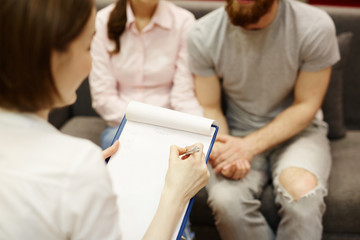 Family psychologist consulting young couple in trouble