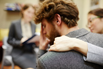 Stressed man touching his face with wife hand on his shoulder