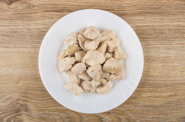 Pieces of boiled chicken meat in white plate on table