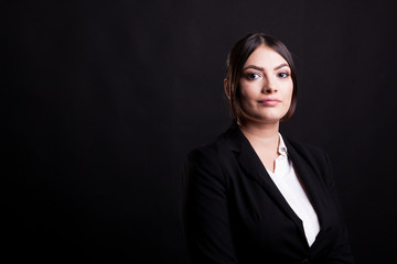 Businesswoman in suit in studio photo over black background
