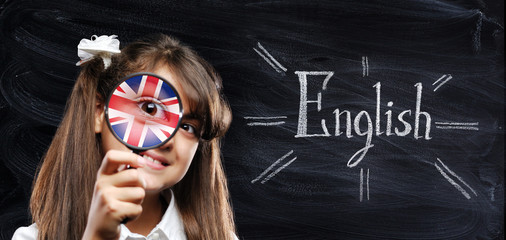 Girl with a magnifier with a british flag reflection on chalk board background
