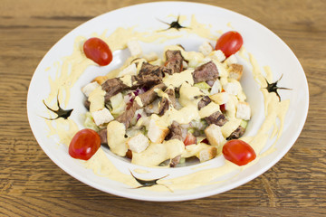 Healthy grilled red meat salad with cheese and croutons. Bacon and lettuce slices in a white plate on a wooden table.