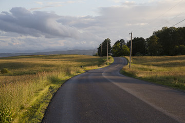USA, Hyde Park, Vermont. A deserted country road lit by a setting sun after rainfall.