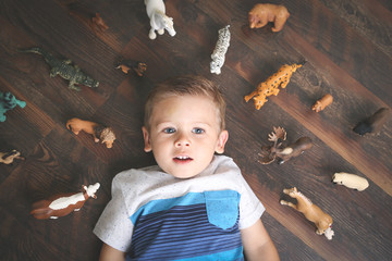Little boy lying down surrounded by animal toys