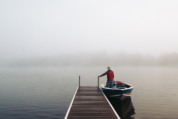 Man standing with boat near a dock on foggy lake.
