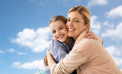 happy family of girl and mother hugging over sky