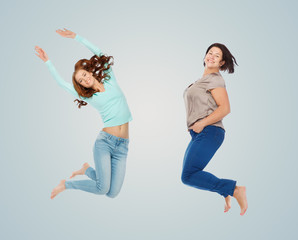 happy different women jumping over blue