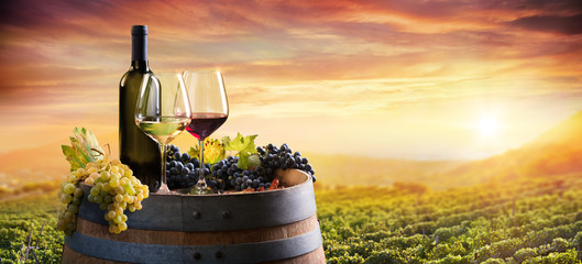 Canvas Prints Honey Bottle And WineGlasses On Barrel In Vineyard At Sunset