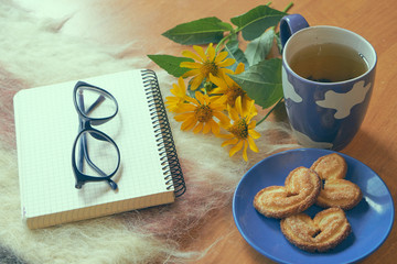 notepad with glasses and cup of tea with cookies
