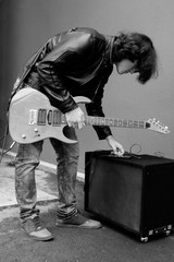 Man in leather jacket with guitar setting music