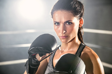 Portrait of an attractive strong competitive female athlete in mixed martial arts and boxing ring