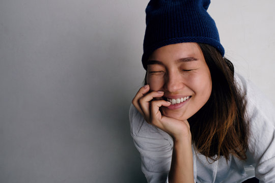 Cheerful Asian woman in blue hat and hoodie smiling with eyes closed