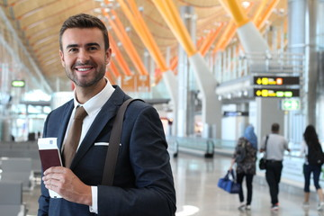 Handsome businessman smiling at the airport with space for copy