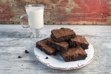 Brownies in rustic setting with glass of milk