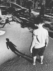 A boy looking at his very long shadow