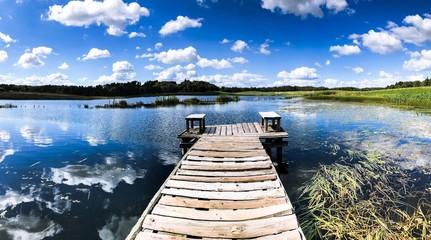 Fototapeta Stary drewniany most nad stawem, błękitne niebo z białymi chmurami odbijają się w tafli wody, na horyzoncie zielona trawa obraz