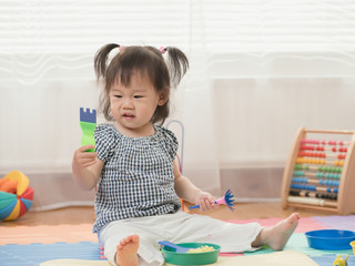 Baby girl play finger paints at home