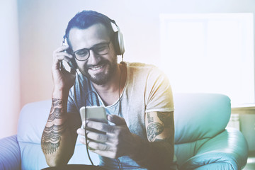 smiling man listening to music with headphones and smart phone