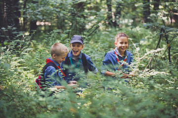 A Girl and Two Boys Playing in The Woods