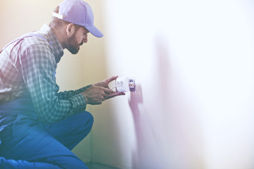 Service man installing power socket in wall with screwdriver. Copyspace for text