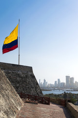 Colombian flag waving on the wind and modern Cartagena district behind it.