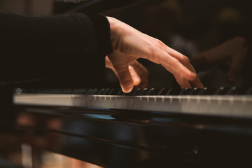 Close-up of woman's hands playing the piano