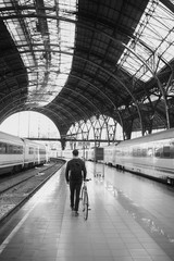 Young man with his bike walking away on the train platform