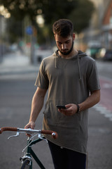 Young man with bike in the street messaging with the phone