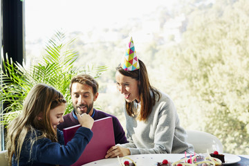 Parents Looking At Daughter Opening Birthday Present