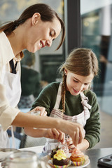 Mother And Daughter Decorating Cupcakes With Sprinkles