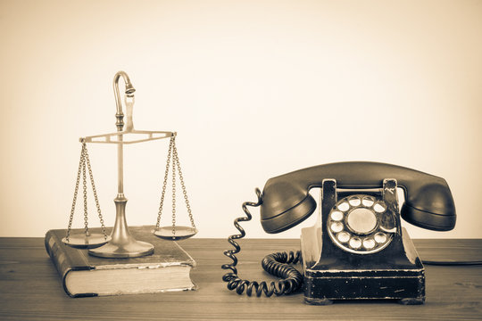 Law scales, old book and retro telephone on table. Vintage style sepia photo